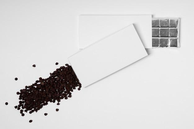 Vista dall'alto di più pacchetti di barrette di cioccolato vuote con pellicola e gocce di cioccolato