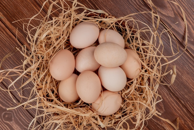 Top view of multiple chicken eggs on nest on a wooden background