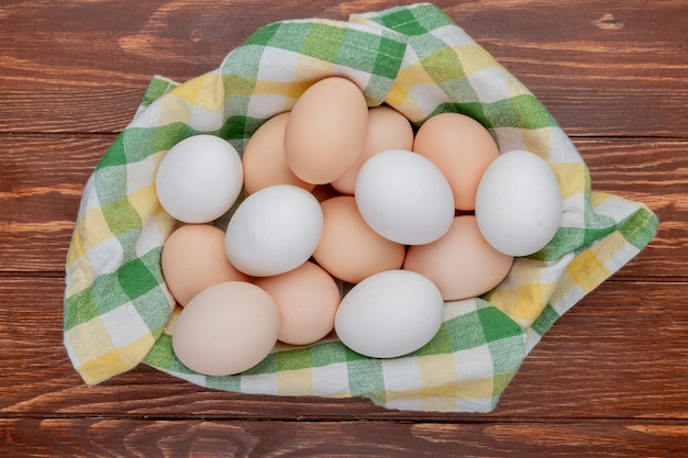 Top view of multiple fresh chicken eggs on checked tablecloth on a wooden background