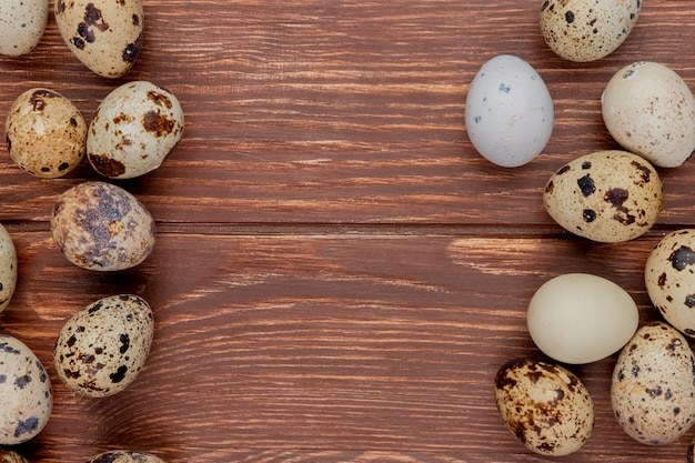 Top view of multiple fresh quail eggs isolated on a wooden background with copy space
