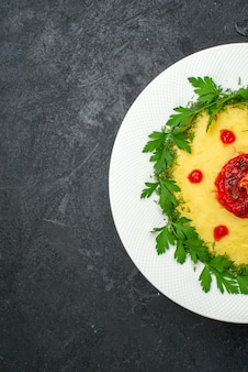 Top view of mushed potato dish with tomato sauce and greens on dark floor dinner dish meal potato