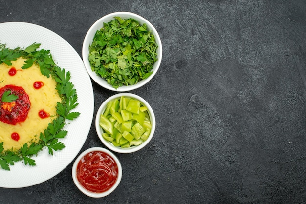 Top view of mushed potato dish with tomato sauce and greens on dark grey