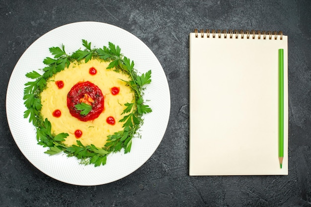 Top view of mushed potato dish with tomato sauce and greens on dark table