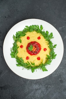 Top view of mushed potato dish with tomato sauce and greens on dark
