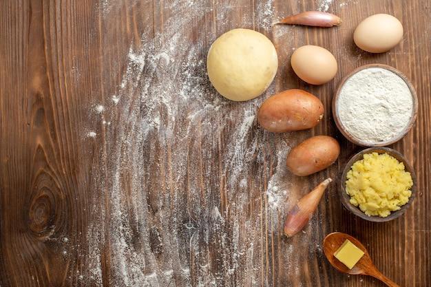 Картофельное пюре с мукой и картофелем на коричневом деревянном столе, вид сверху, острый перец, спелая картофельная еда