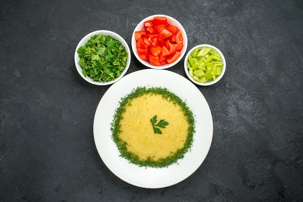 Top view of mushed potatoes with greens and sliced tomatoes on grey floor