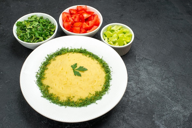 Top view of mushed potatoes with greens and sliced tomatoes on grey table