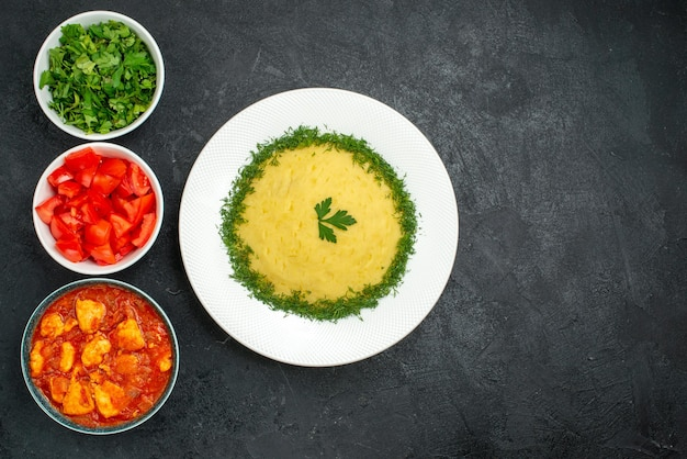 Top view of mushed potatoes with greens and sliced tomatoes on grey