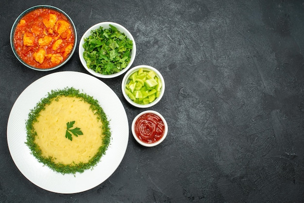 Top view of mushed potatoes with greens and tomato sauce on grey