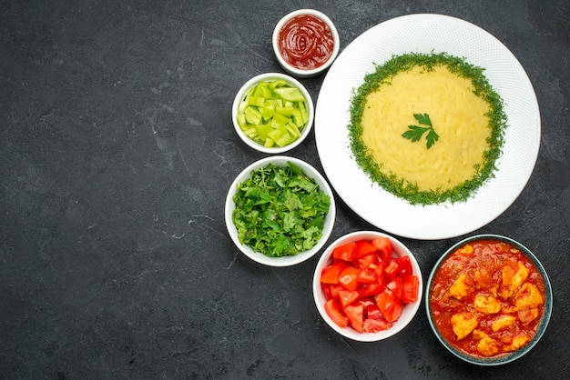 Top view of mushed potatoes with greens and tomatoes on grey