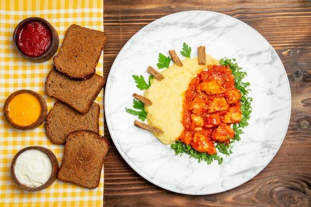 Vista dall'alto di purè di patate con fette di pollo al sugo e pane su piatto di patate da tavola marrone cena a base di carne