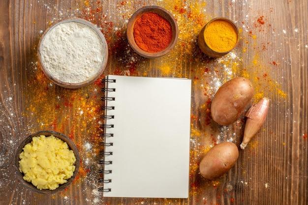 茶色の木製の机の上に調味料を入れたマッシュポテトの上面図スパイシーペッパー熟したジャガイモ食品