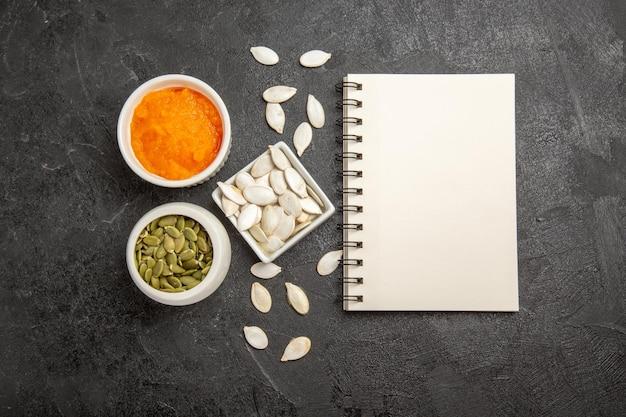 Zucca schiacciata vista dall'alto con semi e blocco note su sfondo grigio quaderno di foto di semi di colore arancione maturo