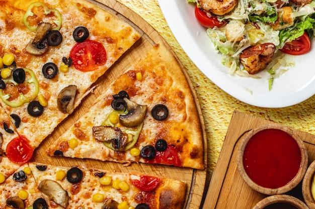 보드에 검은 올리브 옥수수 피망 토마토와 치즈와 함께 상위 뷰 버섯 피자