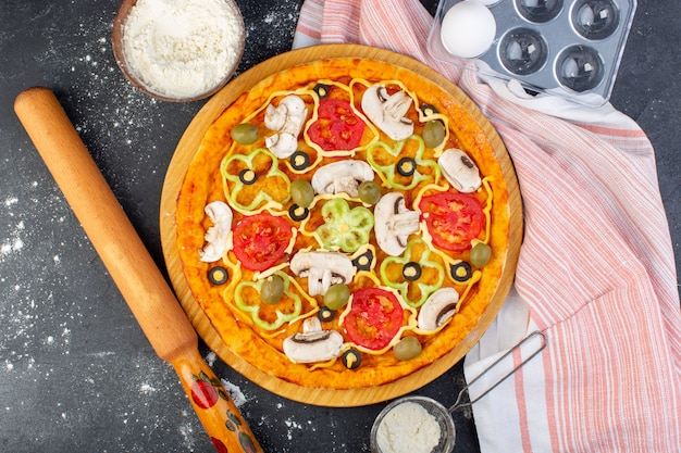 Vista dall'alto pizza ai funghi con pomodori rossi olive tutte tagliate all'interno con olio e farina sulla scrivania grigia impasto per pizza italiano