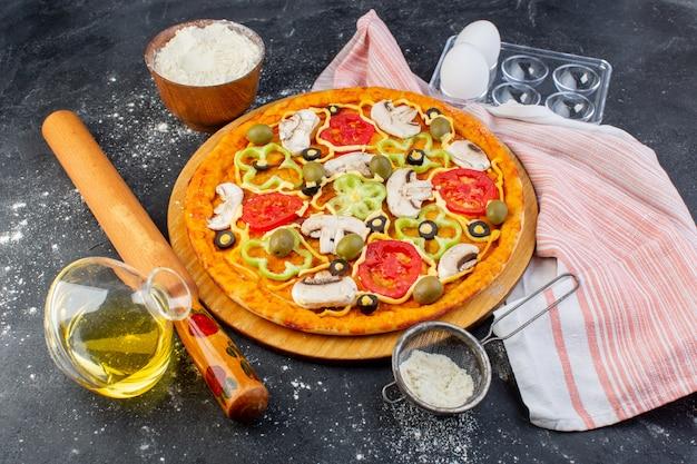 Вид сверху грибная пицца с красными помидорами, маслинами, грибы, нарезанные внутри маслом на сером фоне, тесто для пиццы итальянское