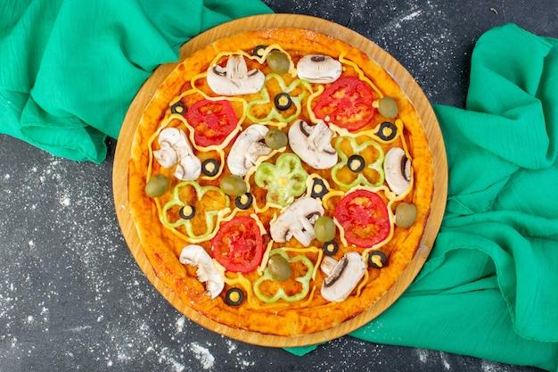 トップビューキノコピザと赤いトマトオリーブキノコすべてが灰色の机の上の油で内部スライスされたグリーンティッシュピザ生地イタリア語