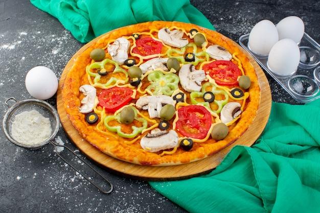 Vista dall'alto pizza ai funghi con pomodori olive funghi tutti affettati all'interno con farina sulla scrivania grigia pasta per pizza con tessuto verde italiano