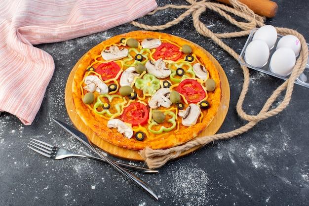 灰色の机の上に卵と一緒にトマトオリーブキノコとキノコのピザのトップビューピザ生地イタリア料理