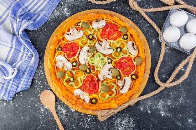 トップビューキノコピザトマトオリーブキノコの卵と暗い机のピザピザ生地イタリア料理