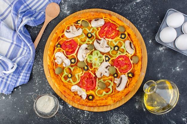 灰色の机の上に小麦粉とトマトオリーブキノコとキノコのピザのトップビューピザ生地イタリア料理