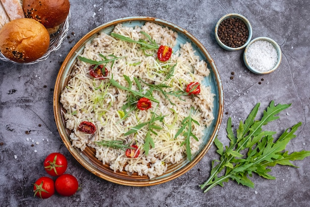 Top view of mushroom risotto garnished with shredded cheese, dried tomato and leaves