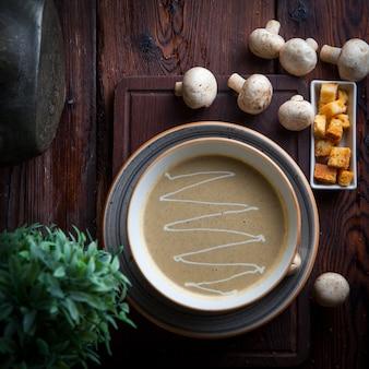Вид сверху грибной суп с крекерами