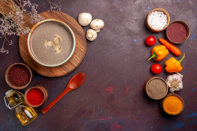 Top view mushroom soup with different seasonings on the dark space
