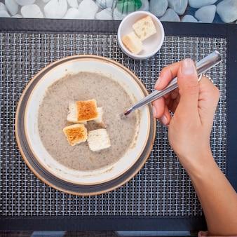 スプーンで石の手で飾られたガラステーブルの上のキノコとトップビューマッシュルームスープ
