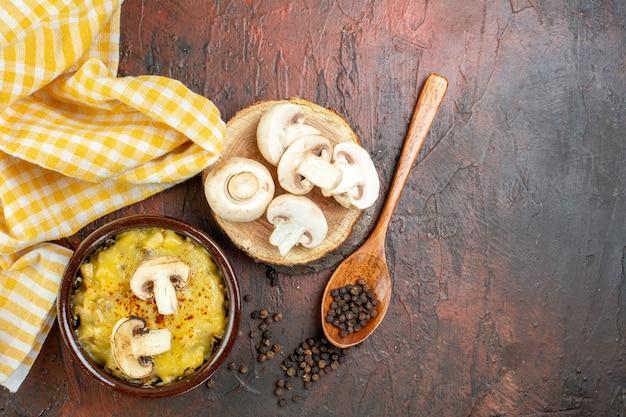 Fungo vista dall'alto con mosarella in ciotola pepe nero in funghi cucchiaio di legno su tavola di legno tovaglia gialla su tavolo rosso scuro