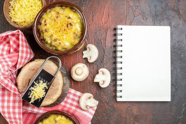 ボウルにモサレラが入った上面のキノコ木のスプーンに黒胡椒を入れたキノコメモ帳おろし金を濃い赤のテーブルに