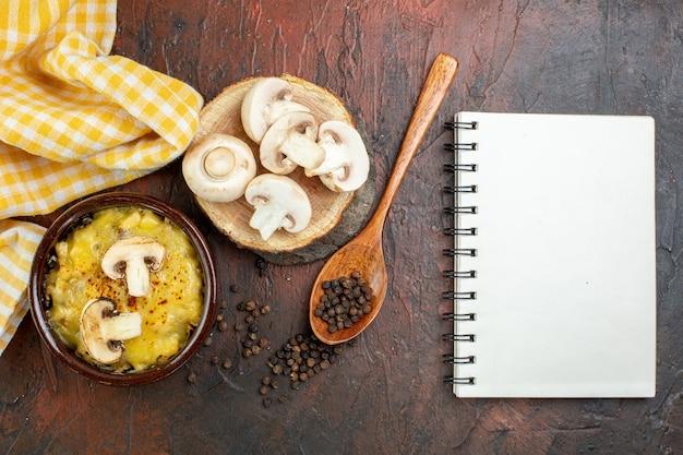 ボウルにモサレラが入った上面図キノコ木のスプーンに黒コショウダークレッドのテーブルに木の板のノートにキノコ