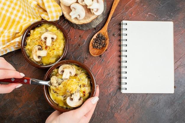 어두운 빨간색 테이블에 여성 손 메모장 나무 숟가락에 그릇 포크에 모사렐라와 상위 뷰 버섯