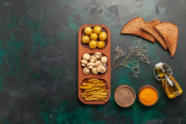 Top view mushrooms and olives with seasonings and bread loafs on the dark background ingredient product meal food