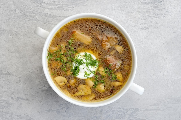 Top view of mushrooms and potato soup with sour cream