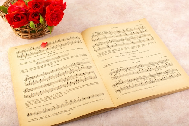 A top view music notes book open along with red roses on pink