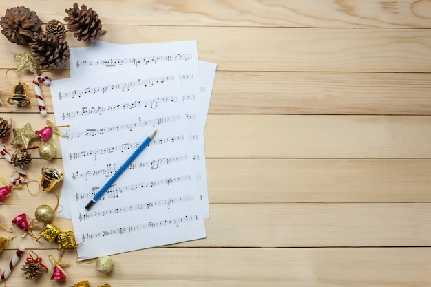 Top view music sheet note paper and christmas decoration on wood background