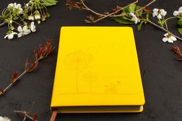 Top view mustard copybook around white flowers on the dark