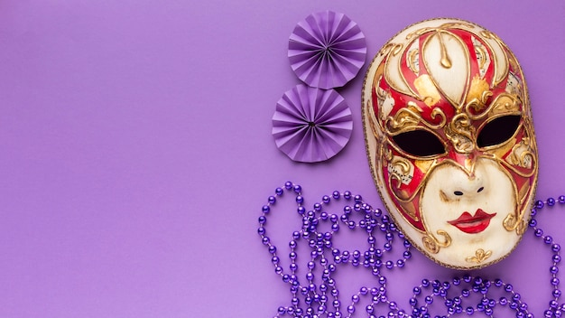 Top view mystery carnival luxury mask and pearls
