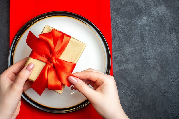 Top view of national christmal meal background with hand holding empty plates with bow-shaped red ribbon on a red napkin on black table