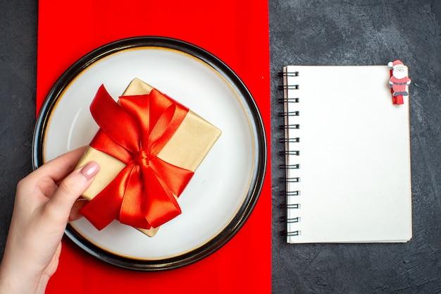 Vista dall'alto dello sfondo del pasto natalizio nazionale con la mano che tiene i piatti vuoti con un nastro rosso a forma di fiocco su un tovagliolo rosso e un taccuino sulla tavola nera