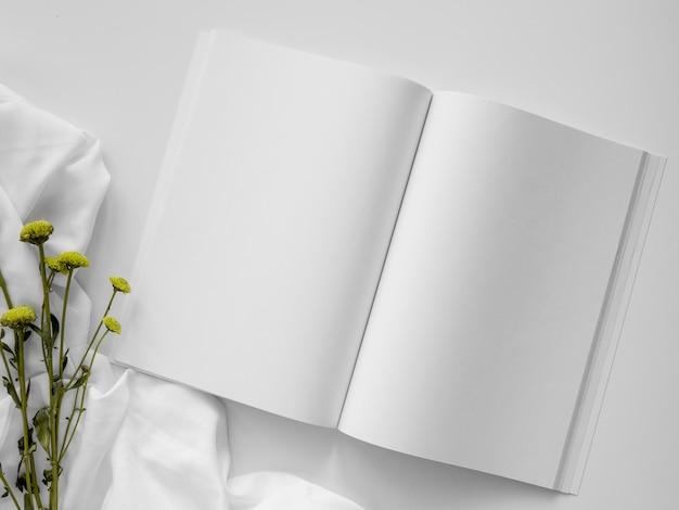 Вид сверху натуральные листья и ассортимент белого журнала