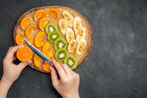 Vista dall'alto della frutta fresca biologica naturale allegata sul tagliere sul lato destro su sfondo scuro