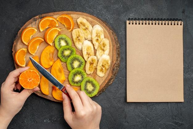 Vista dall'alto della frutta fresca biologica naturale allegata su tagliere e quaderno a spirale su sfondo scuro