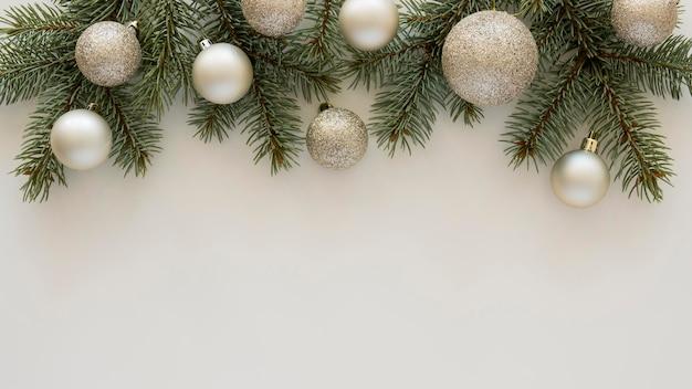 Вид сверху натуральные сосновые иглы и новогодние шары