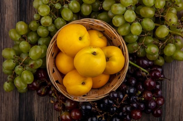 Vista dall'alto di nectacots nel cesto con uva bianca e nera intorno su fondo di legno