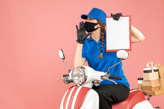 Vista dall'alto della ragazza del corriere nervoso che indossa maschera medica e guanti seduto su uno scooter con un foglio di carta vuoto che consegna ordini su sfondo color pesca pastello