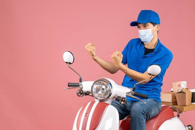 Top view of nervous courier man in medical mask wearing hat sitting on scooter on pastel peach background