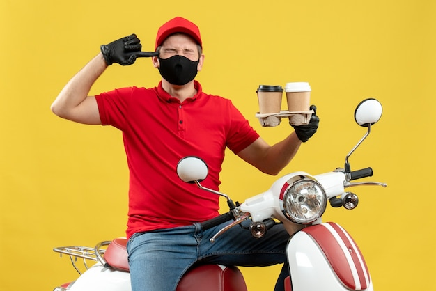 Top view of nervous delivery guy wearing uniform and hat gloves in medical mask sitting on scooter showing orders