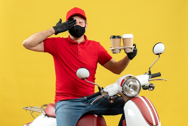 Top view of nervous emotional delivery guy wearing uniform and hat gloves in medical mask sitting on scooter showing orders